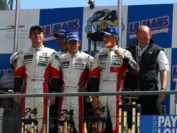 Tom Kristensen (DEN) / Seiji Ara (JPN) / Rinaldo Capello (ITA) Audi Sport Japan Team Goh Audi R8 on the podium after winning the 24 Hours of Le Mans.Le Mans 24 Hours, Le Mans, France, 12-13 June 2004.DIGITAL IMAGE