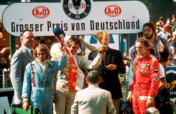 1975 German Grand Prix.Nurburgring, Germany.1-3 August 1975.Carlos Reutemann (Brabham BT44B-Ford) 1st position, Jacques Laffite (Williams FW04-Ford) 2nd position and Niki Lauda (Ferrari 312T) 3rd position, on the podium, portrait.  World Copyright: LAT Photographic.  Ref: 75 GER 02.