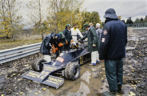 Marshals and team members assess how to remove Derek Daly's Ensign N177 Ford from the mud.