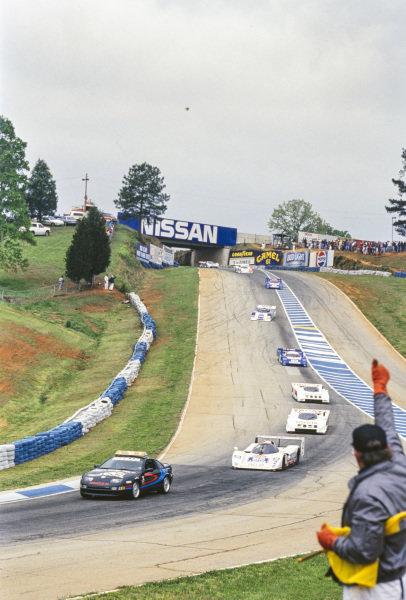 Davy Jones, Jaguar XJR-14, leads Juan Manuel Fangio II, All American Racers, Eagle Mk III Toyota, P. J. Jones, All American Racers, Eagle Mk III Toyota, and Geoff Brabham, Nissan NPT-91 A, behind the pace car.