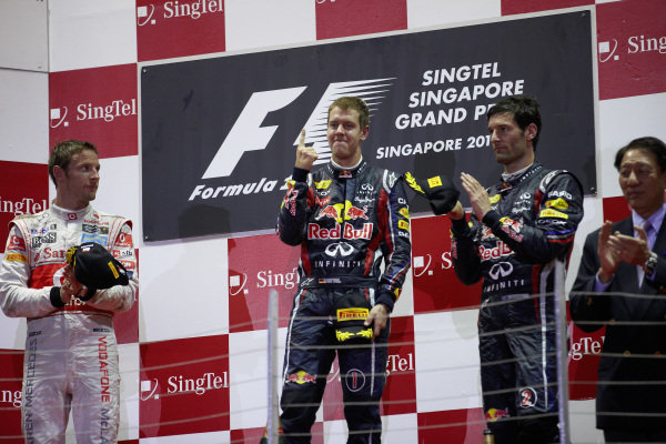 Sebastian Vettel, 1st position, celebrates on the podium with Jenson Button, 2nd position, and Mark Webber, 3rd position.