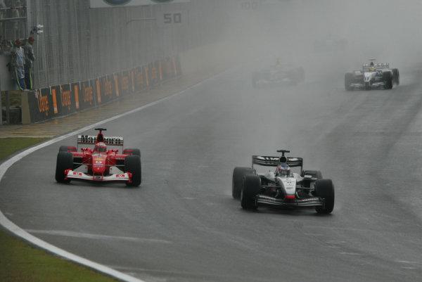 2003 Brazilian Grand Prix. Interlagos, Sao Paulo, Brazil.4-6 April 2003.Kimi Raikkonen (McLaren MP4/17D Mercedes) battles with Rubens Barrichello (Ferrari F2002).World Copyright - Steve Etherington/LAT Photographic ref: Digital Image Only