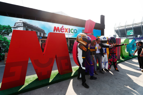 Autodromo Hermanos Rodriguez, Mexico City, Mexico. Sunday 29 October 2017. Fans pose with helmeted mascots in front of a large Mexico sign. World Copyright: Sam Bloxham/LAT Images  ref: Digital Image _W6I0533