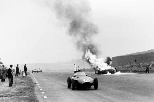 1956 British Grand Prix.Silverstone, Great Britain. 14 July 1956.Tony Brooks's BRM P25 burns after he had crashed as the car of Harry Schell, Vanwall VW2, retired, passes, accident, fire, action.World Copyright: LAT PhotographicRef: Autosport b&w print. Published: Autosport, 20/7/1956 p75