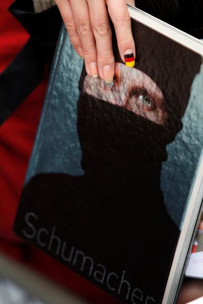 Shanghai International Circuit, Shanghai, China15th April 2010A fan waits to get her Schumacher book signed. Atmosphere. World Copyright: Andrew Ferraro/LAT Photographicref: Digital Image _Q0C5287