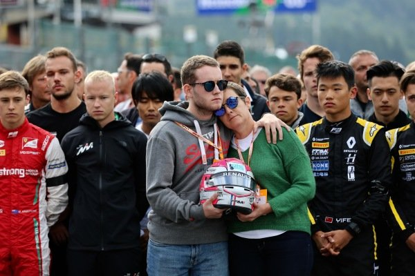 The mother of Anthoine Hubert (FRA, BWT ARDEN) stands with his brother holding his race helmet.
