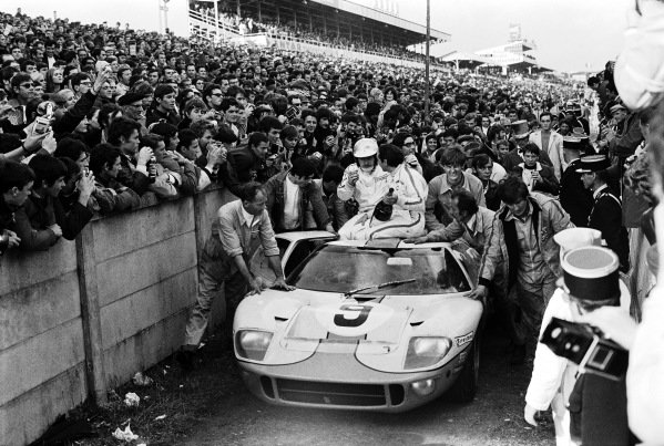 The Pedro Rodriguez / Lucien Bianchi, J. W. Automotive Engineering Ltd., Ford GT40 is pushed through the crowds after claiming victory.