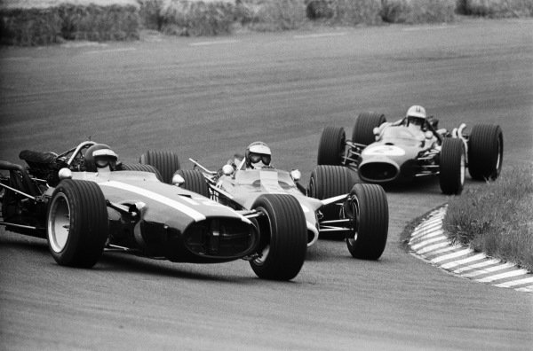 Jochen Rindt, Cooper T81B Maserati, under pressure from Jim Clark, Lotus 49 Ford, and Denny Hulme, Brabham BT20 Repco.