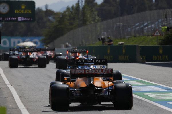 Max Verstappen, Red Bull Racing RB16B, leads Fernando Alonso, Alpine A521, and Daniel Ricciardo, McLaren MCL35M