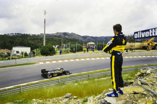 Ayrton Senna stands on some rocks while watching teammate Elio de Angelis, Lotus 97T Renault, drive by.