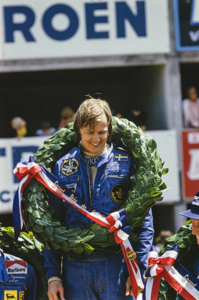Ronnie Peterson celebrates victory on the podium.