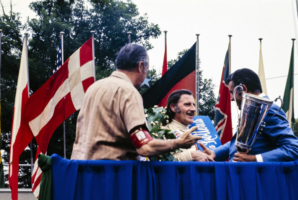 Graham Hill, 1st position, is congratulated on the podium.