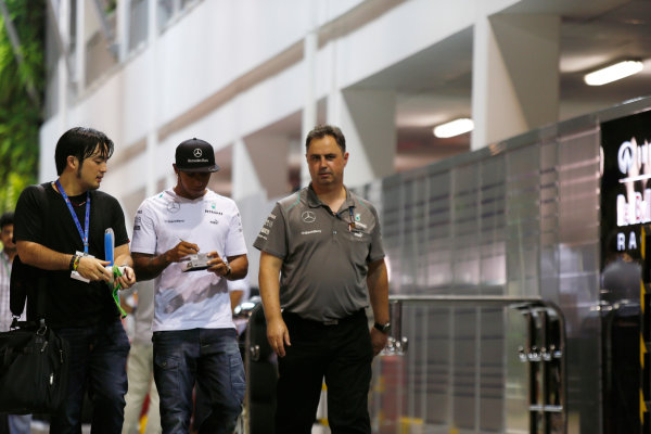 Marina Bay Circuit, Singapore. Friday 20th September 2013. Lewis Hamilton, Mercedes AMG signs an autograph as he walks in the paddock with Team Manager Ron Meadows. World Copyright: Charles Coates/LAT Photographic. ref: Digital Image _N7T3060