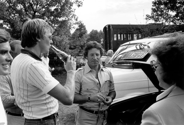 Monza, Italy. 10 September 1978. Mario Andretti gives Colin Chapman and Ronnie Peterson a drink from his Rolls-Royce in the paddock, portrait.  World Copyright: LAT Photographic Ref: L78 - 1423 - 16.