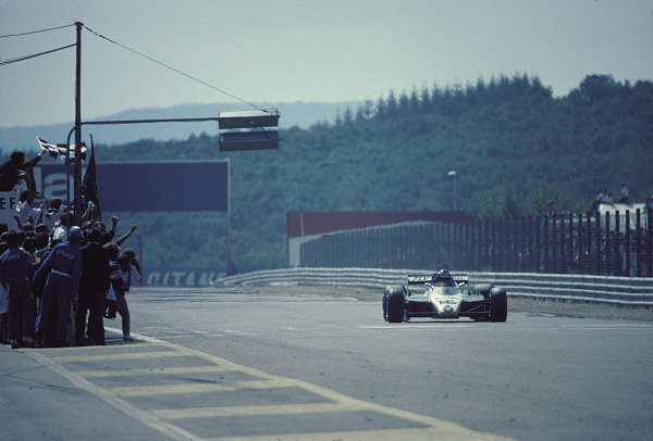 Keke Rosberg, Williams FW08 Ford, celebrates victory as he takes the chequered flag.