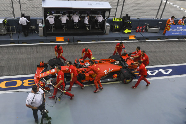 The Ferrari team move Charles Leclerc, Ferrari SF90, in the pit lane