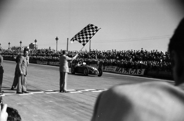 Juan Manuel Fangio, Alfa Romeo 159, takes the chequered flag for victory.