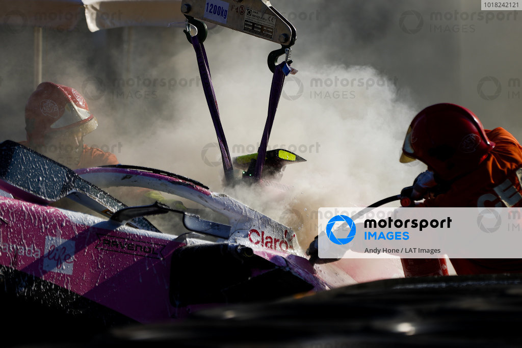 Fire marshals extinguish the car of Lance Stroll, Racing Point RP20