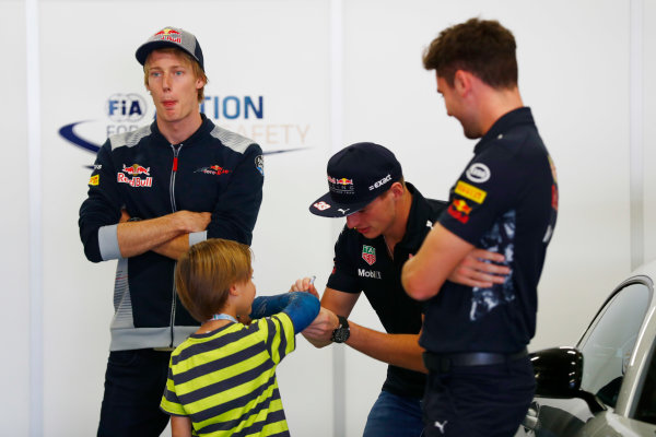 Autodromo Hermanos Rodriguez, Mexico City, Mexico. Sunday 29 October 2017. Max Verstappen, Red Bull Racing, signs an autograph for a young fan, as Brendon Hartley, Toro Rosso, looks on. World Copyright: Sam Bloxham/LAT Images  ref: Digital Image _J6I9705