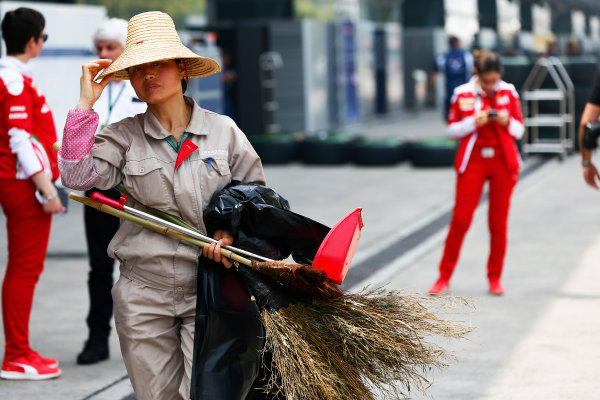 Shanghai International Circuit, Shanghai, China. Thursday 14 April 2016. A worker at the Shanghai Circuit carrying an assortment of cleaning equipment is pictured in front of Ferrari team members. World Copyright: Andy Hone/LAT Photographic ref: Digital Image _ONY2990