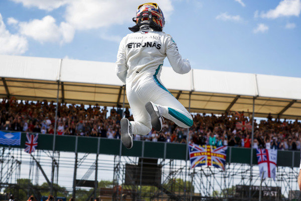 Lewis Hamilton, Mercedes AMG F1, jumps from his car in Parc Ferme as he celebrates taking Pole Position.