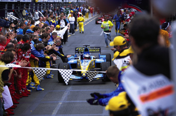 Fernando Alonso, Renault R24, is given a guard of honour by the Renault and Ferrari teams as he enters parc ferme.