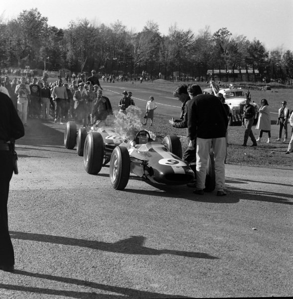The engine of Trevor Taylor, Lotus 25 Climax, catches fire. Pedro Rodríguez's Lotus 25 Climax is behind.