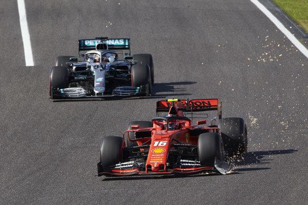 Charles Leclerc, Ferrari SF90, drags a sparking front wing endplate, ahead of Lewis Hamilton, Mercedes AMG F1 W10