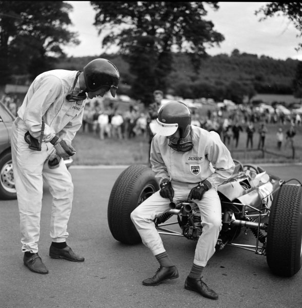 Jim Clark has a conversation with Dan Gurney while sat on the exhaust of his Lotus 25 Climax.