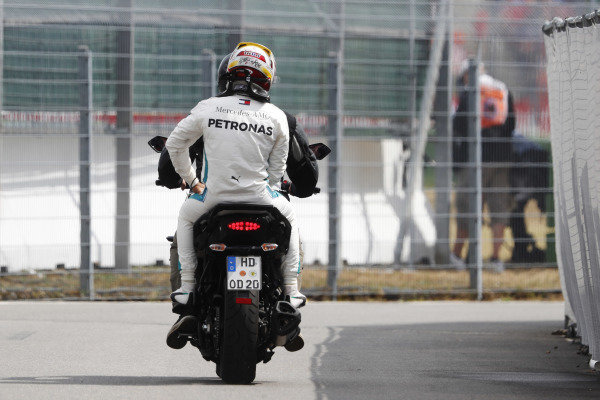 Lewis Hamilton, Mercedes AMG F1, rides back to the pits on the back of a motorcycle after spinning in qualifying.