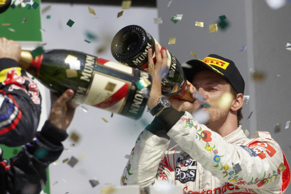 Jenson Button, 3rd position, has a large swig of champagne on the podium.