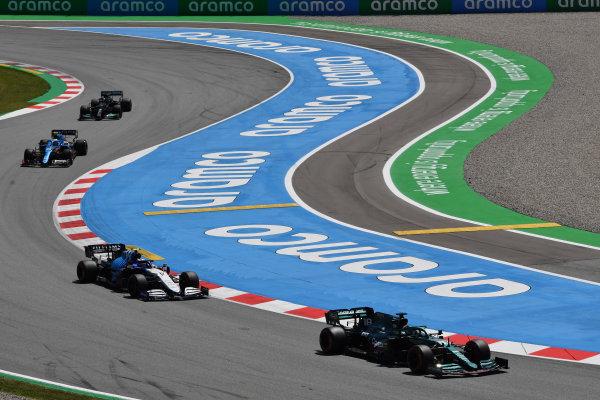 Lance Stroll, Aston Martin AMR21, leads Nicholas Latifi, Williams FW43B, Esteban Ocon, Alpine A521, and Sir Lewis Hamilton, Mercedes W12