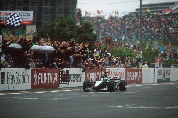 Suzuka, Japan. 29-31 October 1999. Mika Hakkinen (McLaren MP4/14 Mercedes) celebrates victory at the finish. Ref: 99 JAP 03. World Copyright - LAT Photographic