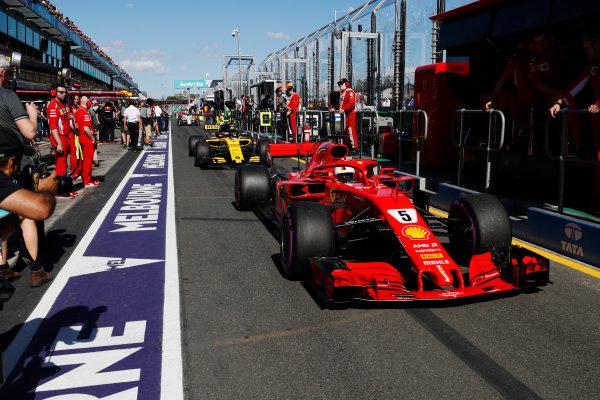 Sebastian Vettel, Ferrari SF71H, leads Carlos Sainz Jr., Renault Sport F1 Team R.S. 18. down the pit lane.
