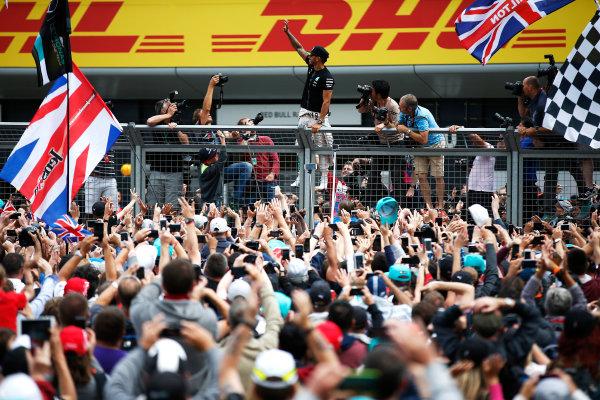 Silverstone, Northamptonshire, England. Sunday 5 July 2015. Lewis Hamilton, Mercedes AMG celebrates with the fans after the race. World Copyright: Glenn Dunbar/LAT Photographic. ref: Digital Image _89P4342