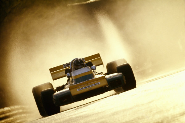 Graham Hill, Brabham BT34 Ford, with backlit spray from the wet track.