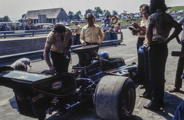 Colin Chapman looks on as mechanics make adjustments to Ronnie Peterson's Lotus 72E Ford.