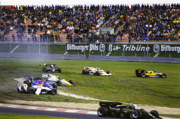 Chaos at the first corner as Gerhard Berger, ATS D7 BMW, Marc Surer, Arrows A7 BMW, Nigel Mansell, Lotus 95T Renault, Jacques Laffite, Williams FW09B Honda, Piercarlo Ghinzani, Osella FA1F Alfa Romeo, and Ayrton Senna, Toleman TG184 Hart, are all caught up in several separate incidents. Elio de Angelis, Lotus 95T Renault, passes by.