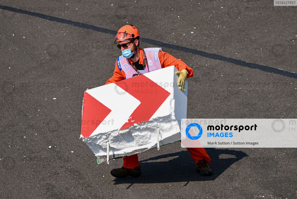 Marshal's piece together broken barrier after Sebastian Vettel, Ferrari SF1000 collided with it