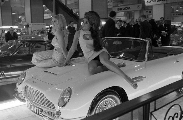 Models on the bonnet of an Aston Martin DB6 Volante.