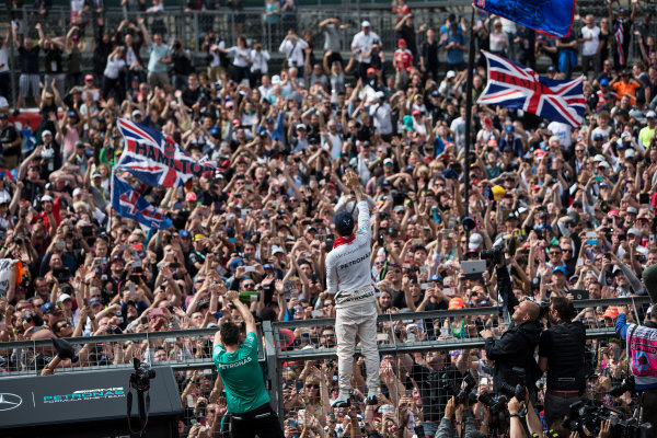Silverstone, Northamptonshire, UK Sunday 10 July 2016. Lewis Hamilton, Mercedes AMG, 1st Position, celebrates victory at his home race with the fans. World Copyright: Ferraro/LAT Photographic ref: Digital Image _FER9106