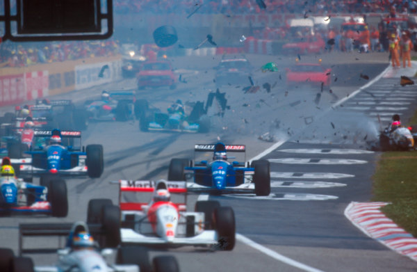 Imola, Italy. 29/4-1/5 1994. Debris flies everywhere as J.J.Lehto's Benetton B194 Ford which was stalled on the grid, was struck by Pedro Lamy (Lotus 107C Mugen-Honda). He had no chance of avoiding him because up until the last second he had not been able to see that there was a stationary car on the grid at all. The rest of the field takes avoiding action.  Ref-94 SM 55. World Copyright - LAT Photographic