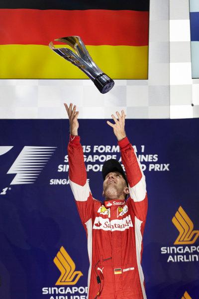 Marina Bay Circuit, Singapore. Sunday 20 September 2015. Sebastian Vettel, Ferrari, 1st Position, tosses his trophy in the air. World Copyright: Steve Etherington/LAT Photographic ref: Digital Image SNE29652