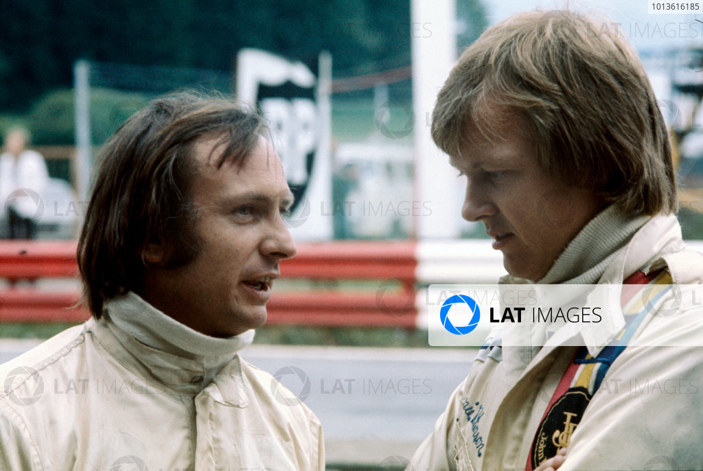 Ronnie Peterson chats to Chris Amon in the pits, portrait. 