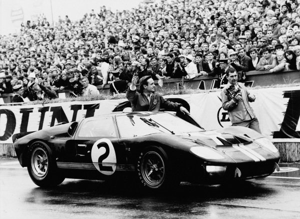 Chris Amon waves to the fans as he celebrates victory in his Shelby American Inc. Ford Mk II shared with Bruce McLaren.