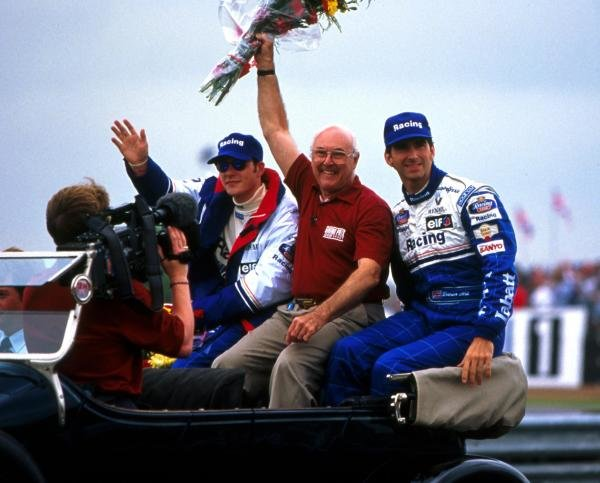 BBC Grand Prix commentator Murray Walker (GBR) waves to the crowds. Beside him are Rothmans Williams drivers Damon Hill (GBR), right, and Jacques Villeneuve (CDN), left. British Grand Prix, Silverstone, England. 14 July 1996.