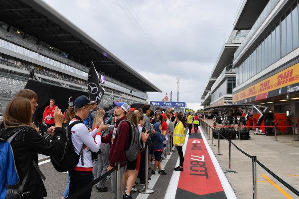 Fans explore the pit lane