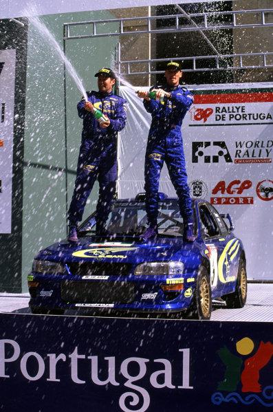 FIA World Rally ChampionshipPortuguese Rally, Porto, Portugal.16-19th March 2000.Richard Burns and Robert Reid celebrating win for Subaru. Podium.World - LAT PhotographicTel: +44 (0) 181 251 3000Fax: +44 (0) 181 251 3001e-mail: latdig@dial.pipex com