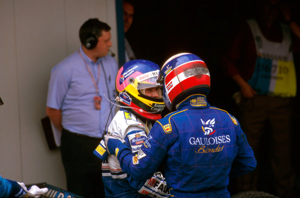 Barcelona, Spain.23-25 May 1997.Olivier Panis (Prost Mugen Honda) 2nd position congratulates Jacques Villeneuve (Williams Renault) 1st position, on his win of the Spanish Grand Prix in parc ferme.Ref-97 ESP 03.World  Copyright - LAT Photographic