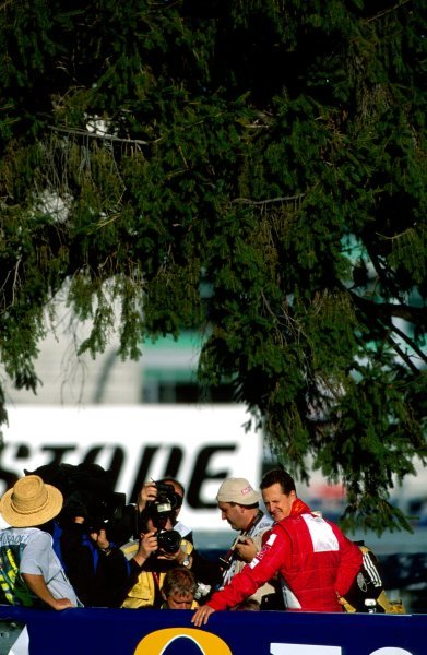 Michael Schumacher (GER) watches the rest of the session from the infield after a mechanical failure with the Ferrari F2002-GAUnited States Grand Prix, Rd15, Indianapolis Motor Speedway, Indianapolis, USA. 28 September 2003.BEST IMAGE